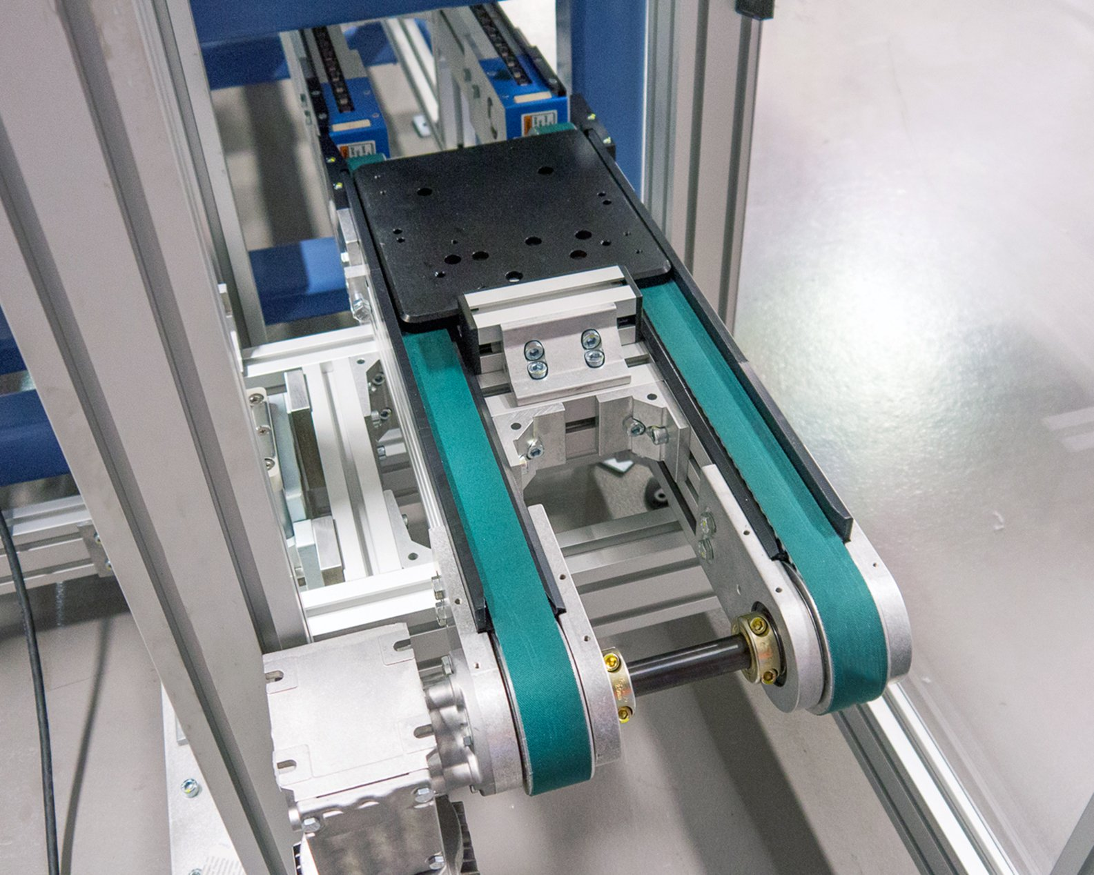 Timing belt conveyor in a vertical transfer unit with a plastic pallet